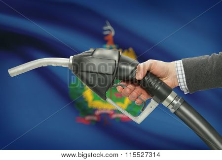 Fuel Pump Nozzle In Hand With Usa States Flags On Background - Vermont