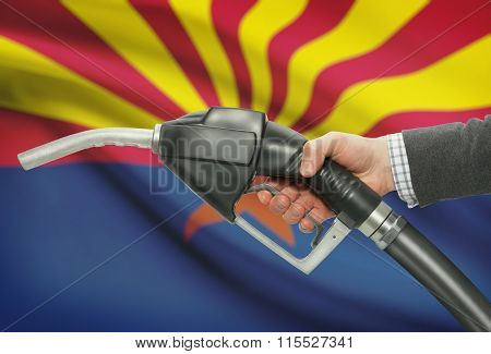 Fuel Pump Nozzle In Hand With Usa States Flags On Background - Arizona