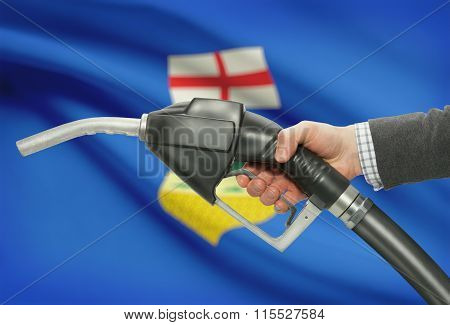 Fuel Pump Nozzle In Hand With Canadian Provinces Flags On Background - Alberta