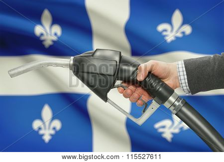 Fuel Pump Nozzle In Hand With Canadian Provinces Flags On Background - Quebec