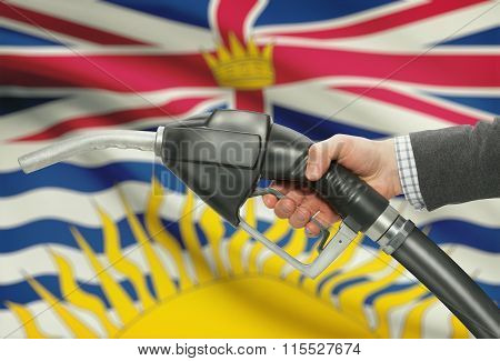 Fuel Pump Nozzle In Hand With Canadian Provinces Flags On Background - British Columbia