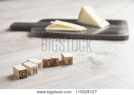 Wooden Letters Cheese In Front Of Marble Board