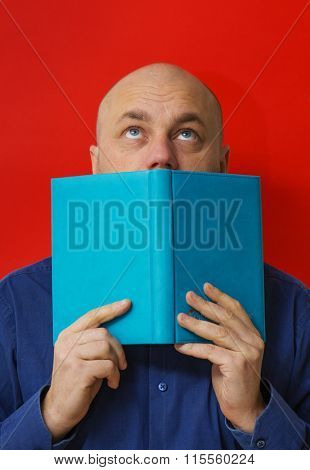 Mature man being focused and hooked by book, reading open book. Lookup. Red background.