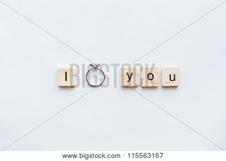 White background with wooden words I LOVE YOU and diamond engagement ring. Good as card or background for Valentine's Day of engagement card. poster