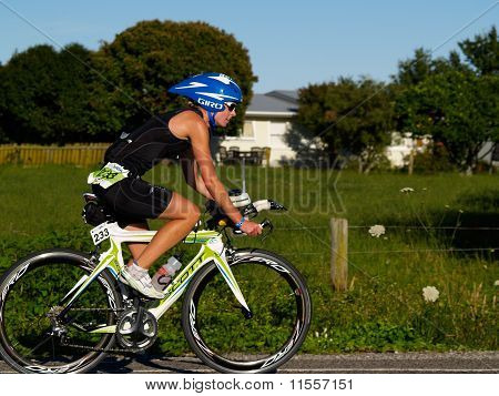 Cyclist pedalls past field and house in event.