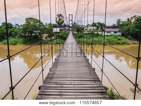 Rope suspension bridge across a river in flood, Thailand