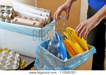 Woman sorting different waste, indoors