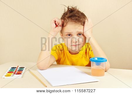 Little preoccupied artist in yellow shirt is thinking what to draw