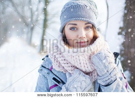 Beautiful  young woman wearing winter hat gloves and scarf covered with snow flakes. Winter forest landscape background