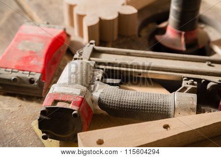 Carpentry tools - nailing gun and sander on a workbench