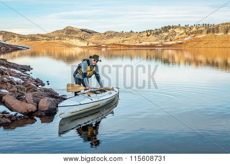 senior male paddler with his decked expedition canoe on a shore  of Horsetooth Reservoir near Fort Collins in northern Colorado, winter scenery