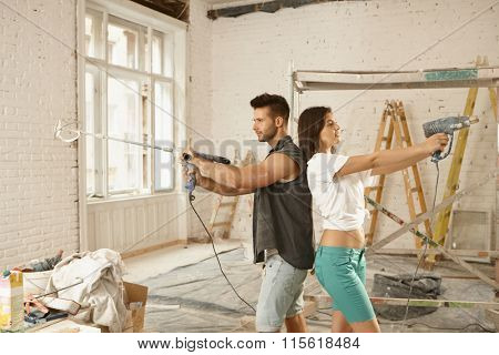 Young couple standing back-to-back, using power drill, renovating home.
