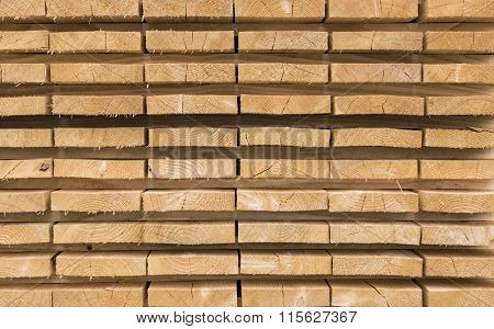Trimmed and debarked timber planks piled up at a sawmill