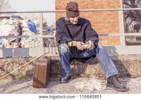 tramp eating bread sitting in landfills