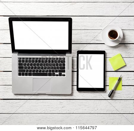 Mockup with tablet pc, open laptop and sticky notes on wood table. Simple creative workspace. Clipping paths included. poster