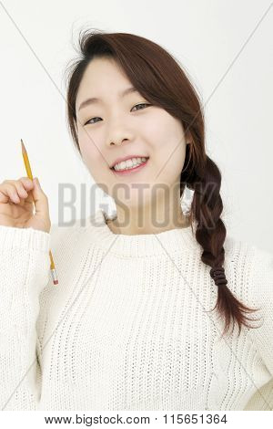 Smiling woman with a yellow pencil