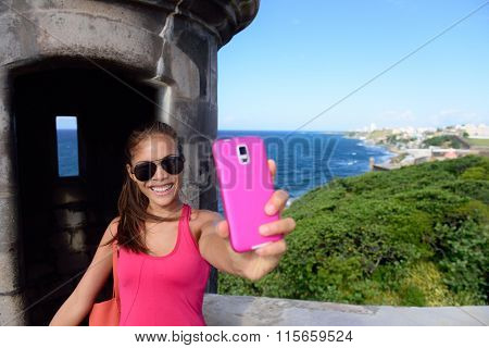 Tourist taking fun selfie at famous landmark. Travel woman holding a pink smartphone visiting Old San Juan's Castillo San Felipe Del Morro, the main attraction of the city of San Juan, Puerto Rico.