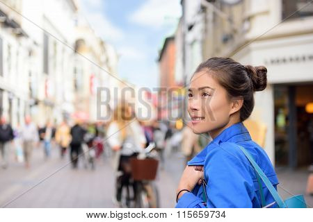 Shopping woman lifestyle in Copenhagen street. Scandinavian travel, tourist adult alone walking looking at shops during fall or spring in famous European city center in Denmark.