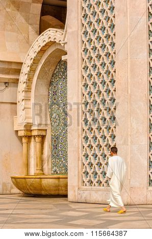CASABLANCA, MOROCCO, APRIL 2, 2015: Local man walks on the outside grounds of Hassan II Mosque or Grande Mosquee Hassan II
