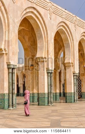 CASABLANCA, MOROCCO, APRIL 2, 2015: Local woman walks on the outside grounds of Hassan II Mosque or Grande Mosquee Hassan II