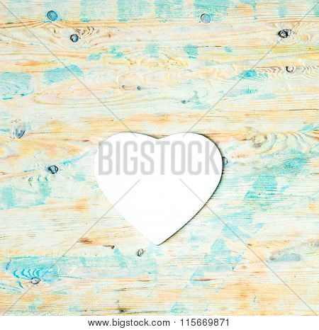 white heart shaped mousepad on wooden background