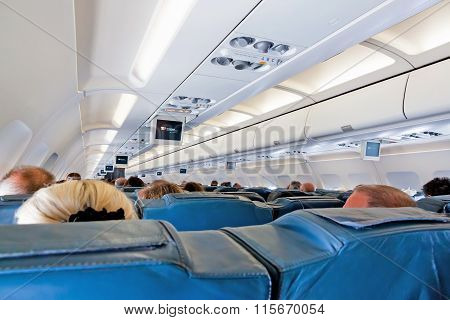 Interior Of Airplane With Passengers On Seats During Flight