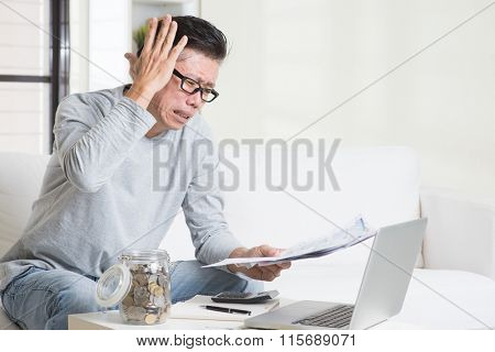 Portrait of 50s mature Asian man having a hard time paying bills. Saving, retirement, retirees financial planning concept. Family living lifestyle at home.