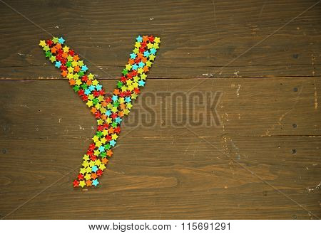 Letter Y from alphabet made with star shape candy on a wooden background