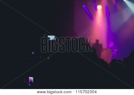 Concert Goer Taking Photos With Mobile Of Rock Band.