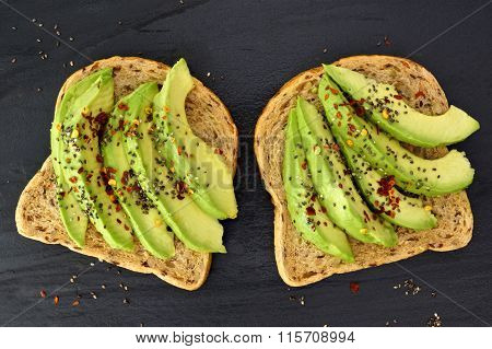 Open avocado sandwiches with chia seeds on dark slate