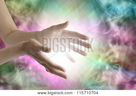 Outstretched female healing hands with white light between and a vibrant multicolored flowing energy field background poster