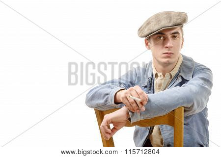 Young  Worker In Vintage Clothing, Sitting On A Chair On A White Background