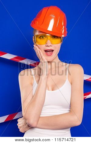 Blonde With Construction Helmet And Goggles On A Blue Background