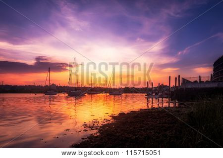 Vibrant Harbor Sunset with Boats on water. poster