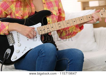 Female Hands Holding And Playing Black Electric Guitar Closeup