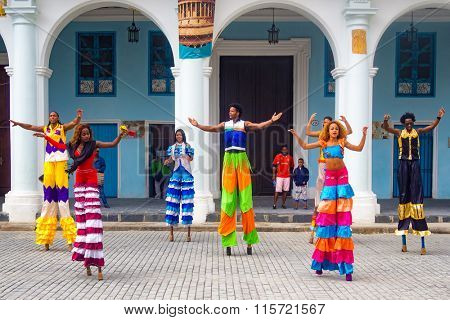 HAVANA,CUBA- JANUARY 24,2015 : Colorful band of street dancers on stilts on a beautiful Old Havana square