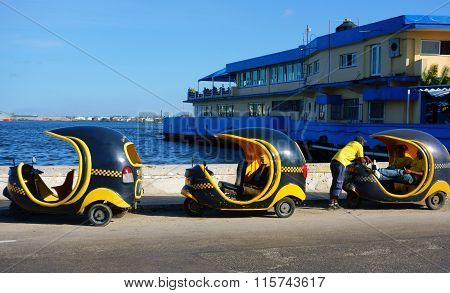 Three Cocotaxis and their drivers in the Havana harbor