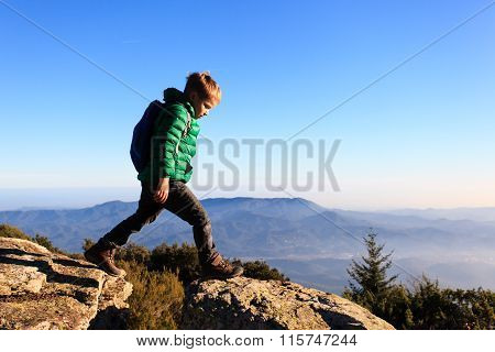 little boy with backpack hiking in scenic mountains