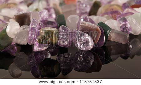 Closeup Crystals Of Amethyst, Fluorite, Jasper, Carnelian And Rose Quartz On Black Table. Selective