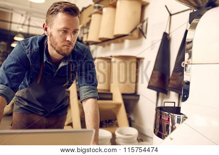 Entrepreneur working in his neat and modern coffee roastery