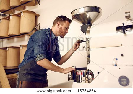 Business owner roasting coffee beans with a modern machine