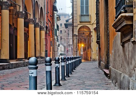 Old street view Bologna city Italy. Cobble stone street with bollards. Renaissance buildings.