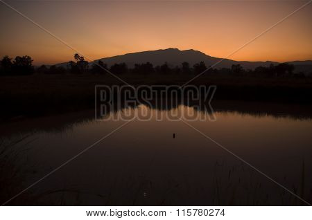 Orange dusk Mountains reflected in lake