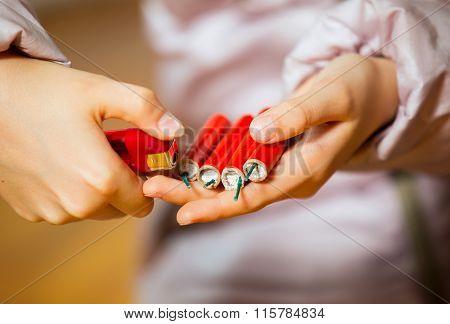 Little girl holding a firecracker. Selective focus.