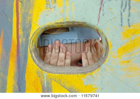 Pretty Little Girl Look Out Of The Hole In Painted Wall.