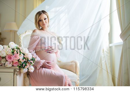 Cute Pregnant Woman Sitting On Chair Near Billowing Curtains And Hugs Belly With Love