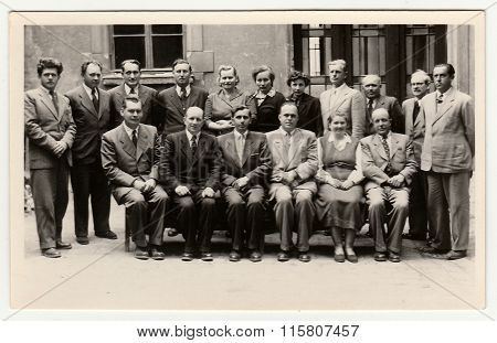 Vintage photo shows group of people in front of building, circa 1960s.