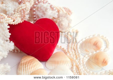 red velvet heart with pearl beads shells and corals on white background with copy space in the top-right corner poster