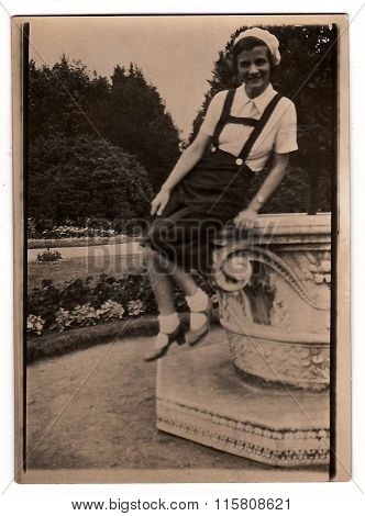 A vintage photo shows young woman sits on a big stone flowerpot in a city park, circa 1930s.