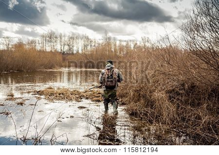 hunter man creeping in swamp during hunting period